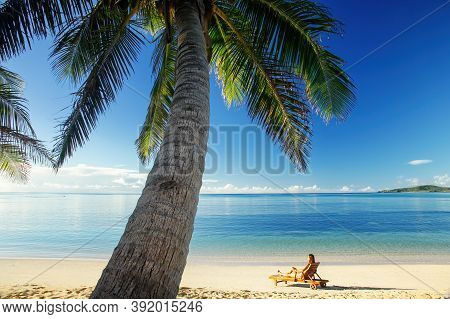 Young Woman Sitting In A Sun Chair On The Beach, Nacula Island, Yasawas, Fiji