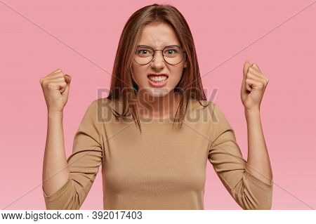 Shot Of Aggressive Woman Raises Hands Clenched In Fists, Argues With Neighbours, Looks Intense And I