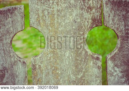 Old Weathered Wooden Fence With Rounded Gaps And Blury Green Background - Scratched Wood Texture