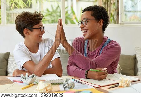 Glad Multiethnic Dark Skinned Woman And Youngster Give High Five To Each Other, Sit At Workplace, Ac