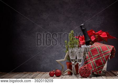 Champagne bottle in bucket with ice, empty champagne flutes and Christmas ornament on dark background with copy space. Christmas. New Year. Design element for greeting card, invitation, advertising