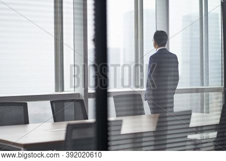 Rear Side View Of An Asian Business Man Standing In Front Of Office Window Looking Out And Thinking