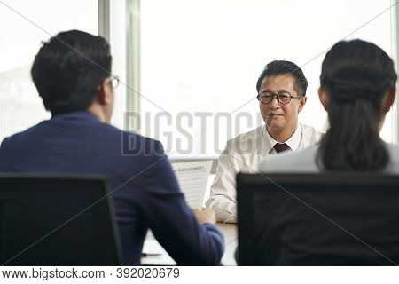 Mature Job Seeker Asian Business Man Being Interviewed By Young Human Resources Executives
