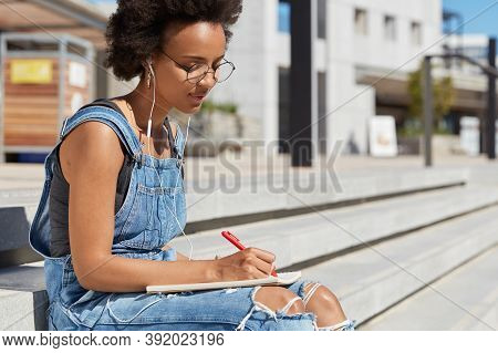 Serious Woman With Dark Healthy Skin, Concentrated On Writing Essay, Holds Pen, Makes Notes In Notep