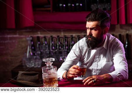 Man With Beard Holds Glass Brandy. Bearded Guy Drink Cognac. Man Holding A Glass Of Whisky. Sipping