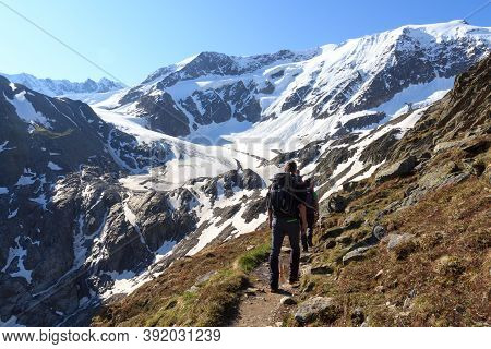 Group Of People Hiking Towards Glacier Taschachferner And Mountain Snow Panorama With Blue Sky In Ty