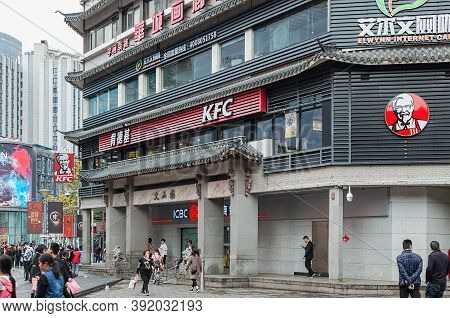 Kfc Restaurant In A Building With Traditional Chinese Architecture. Busy Street With Group Of People