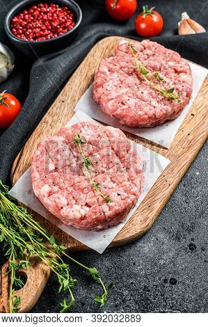 Raw Pork Cutlets, Ground Meat Patty On A Cutting Board. Organic Mince. Black Background. Top View