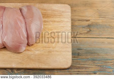 Chicken fillet on a wooden cutting board. Raw, fresh chicken fillet. Chicken fillet cut in the form of a butterfly.Top View.