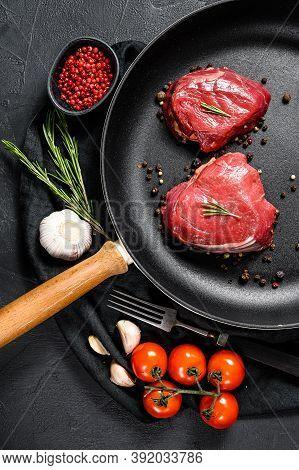 Raw Filet Mignon Steak In A Frying Pan. Beef Tenderloin. Black Background. Top View