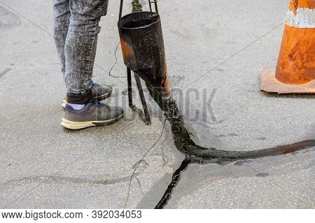 Man Sealing Asphalt Driveway With Filled Cracks Sealcoating Selective Focus