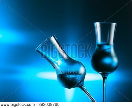 Pouring Alcoholic Drink In Glass With Ice. Steamed Glasses With Strong Alcoholic Drink On A Blue Bac