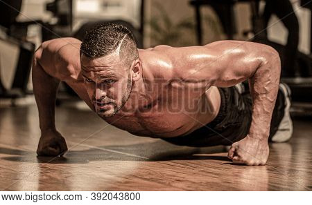 Man Doing Push-ups. Muscular Man Doing Push-ups On One Hand Against Gym Background. Slim Man Doing S