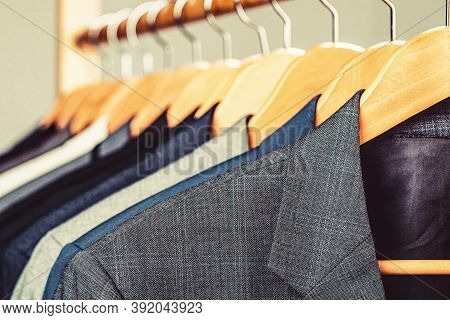 Mens Suits In Different Colors Hanging On Hanger In A Retail Clothes Store, Close-up. Suits For Men