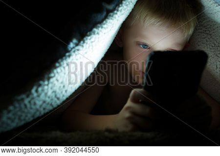 Boy Plays Games On A Smartphone At Night Under A Blanket On The Floor, The Child Rewrites With Frien