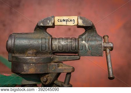 Concept Of Dealing With Problem. Vice Grip Tool Squeezing A Plank With The Word Camping