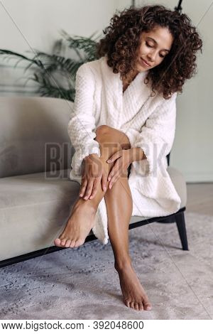 Skincare And Body Care Concept. Vertical View Of Calm African American Woman In Bathrobe Sitting At