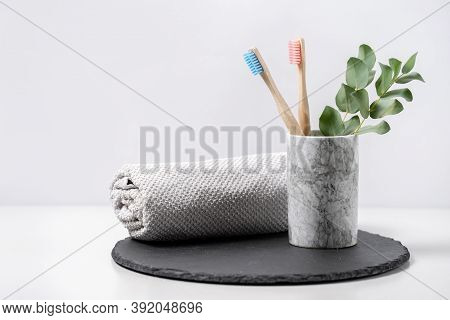 Concept Of Biodegradable Objects. Two Bamboo Toothbrush In Cup Near Bathroom Towel And Eucalyptus Pl