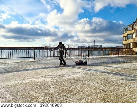 A Boy Rides A Girl On A Sled On The Ice On The Embankment Near The River.