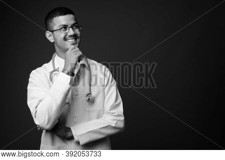 Young Multi Ethnic Asian Man Doctor Against Gray Background