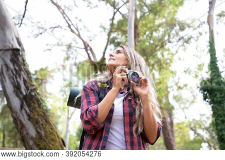 Pretty Young Woman Holding Camera And Looking Around. Happy Female Traveler Hiking With Backpack, Sh