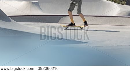 Lower Body Part Of Boy Riding Skateboard In Concrete Skatepark