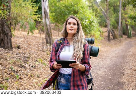 Pretty Tourist Holding Tablet With Map And Looking Away. Caucasian Long-haired Woman Hiking Or Walki