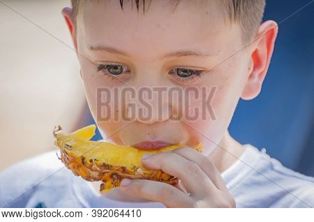 Cute Caucasian 8 Year Old Boy With Blue Eyes Eating Pineapple Close Up Portrait Image.