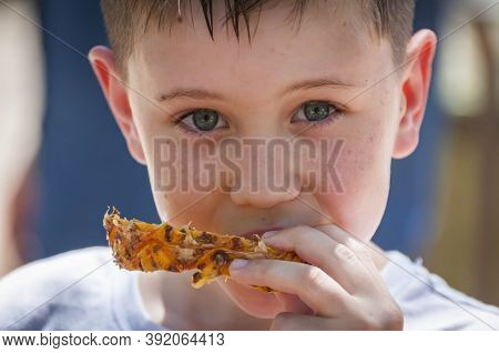 Cute Caucasian 8 Year Old Boy With Blue Eyes Eating Pineapple Looking At The Camera Close Up Portrai