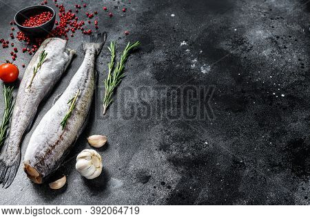 Fresh Pollock Fish. Raw Seafood. Black Background. Top View. Copy Space