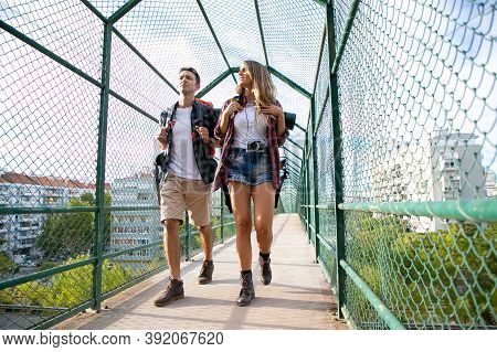 Two People Going On Bridge Surrounded With Green Grid. Caucasian Man And Woman Carrying Backpacks An