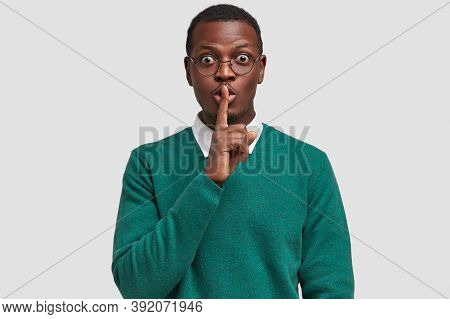 Surprised Attractive Black Man Keeps Index Finger Over Mouth, Demonstrates Silence Sign, Asks Not Te