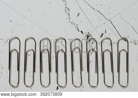 Office Supplies, Nickel-plated Paper Clips On The Textured Surface Of The Table.