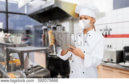 cooking, culinary and health concept - female chef in toque wearing face protective medical mask for protection from virus disease with tablet pc computer over kebab shop kitchen background