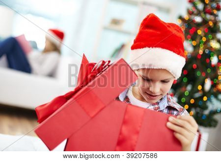 Portrait of curious boy looking inside big red giftbox on Christmas evening