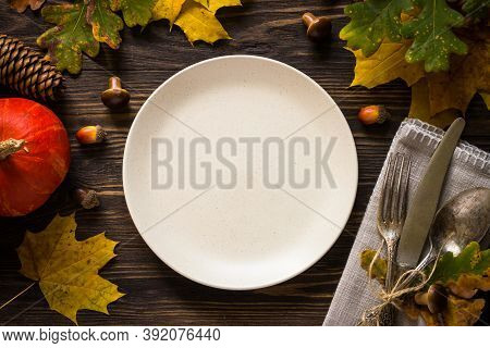 Autumn Table Setting With Craft Plate, Silverware And Fall Decorations. Dark Wooden Table, Toned Ima
