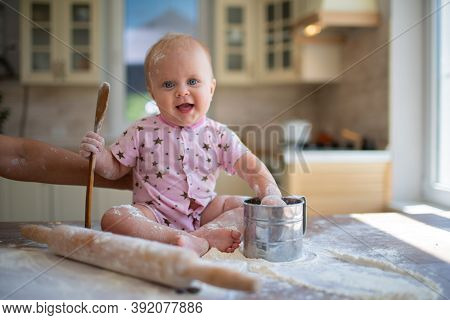 Little child sitting in the kitchen with flour at home