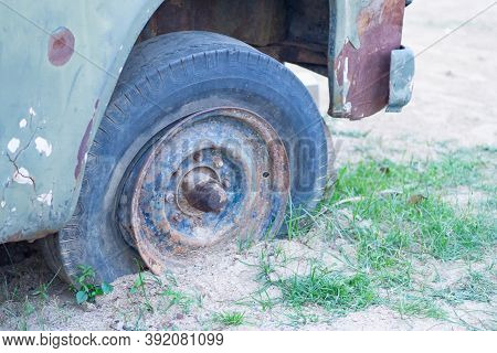 Close-up Of Old Car Wheel Damaged With Rust. Broken And Forgotten. An Old Discarded Rusted Out Scrap