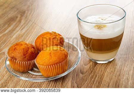 Orange Muffins In Plate, Transparent Glass With Latte-macchiato On Wooden Table