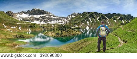 Hiking Man Standing At Remote Lake Up High In The Alpine Mountains. Alps, Bavaria, Schrecksee.