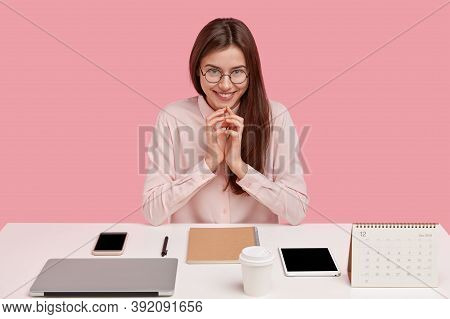 Image Of Satisfied European Lady Office Worker Being Real Perfectionist, Keeps Hands Together, Smile
