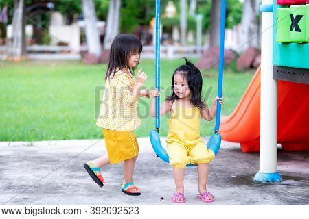 Two Girls Share Swing. The Eldest Is Teaching The Youngest Sister To Swing The Blue Swing. Pretty Ki