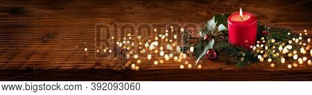 Background For Christmas With Burning Red Candle And Natural Decoration On Rustic Wooden Board. Long