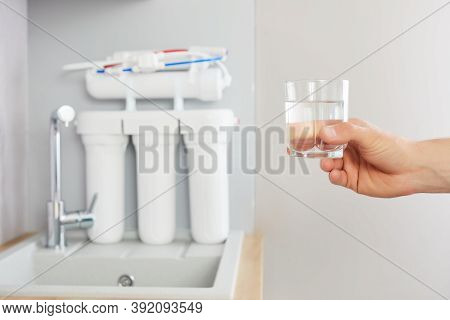 Mens Hand Holds A Glass Of Clear Water. Tap And Reverse Osmosis Filter In The Background.