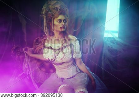 Vampires. Charming and terrible vampire woman in the old abandoned castle in violet haze. Vintage style. Halloween.