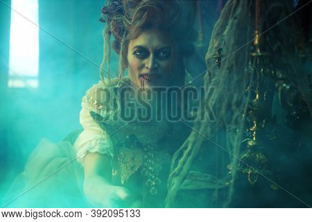 Vampires. Bloodthirsty female vampire in the old abandoned castle in green haze. Vintage style. Halloween.