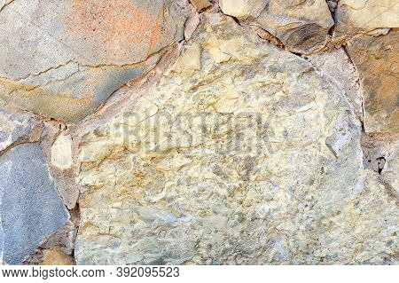 Close-up And Top View Of Masonry Walls Made Of Natural Rough Stones With Voluminous Texture. Backgro