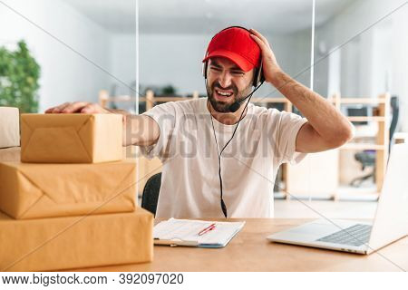 Angry man working in postal parcel delivery service office