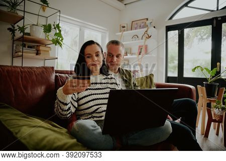 Young Woman Holding Debit Card To Make Online Purchase Transaction With Husband At Home