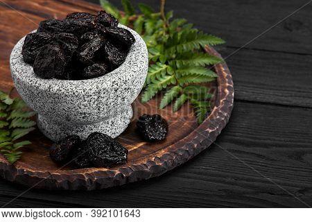 Fresh Prunes In Stone Bowl. Prunes On Stone Dark Table. Prunes Healthy Food. Dried Plums In Bowl.